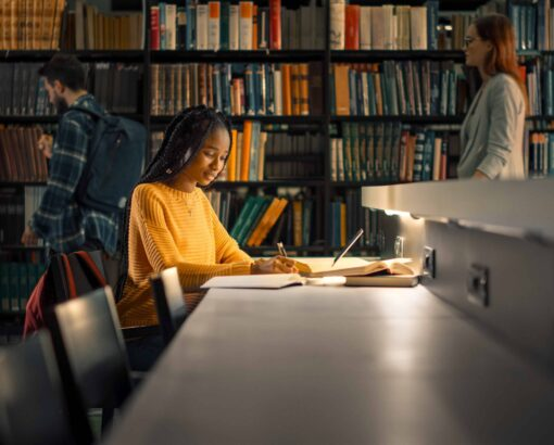 University Library: Gifted Black Girl uses Laptop, Writes Notes for the Paper, Essay, Study for Class Assignment. Students Learning, Studying for Exams College. Side View Portrait with Bookshelves