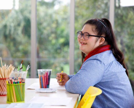 Asian girl with Down's syndrome studying in art class.