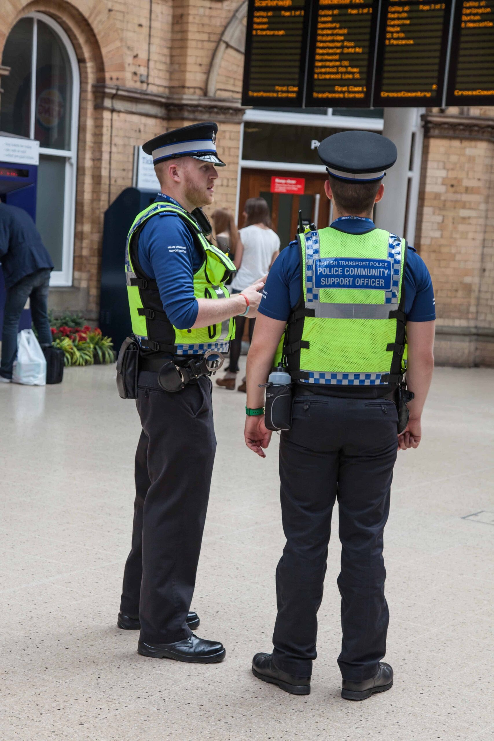 York, England - June 16, 2015: British Transport Police Community Support Officers York Railway Station on the main concourse talking and people